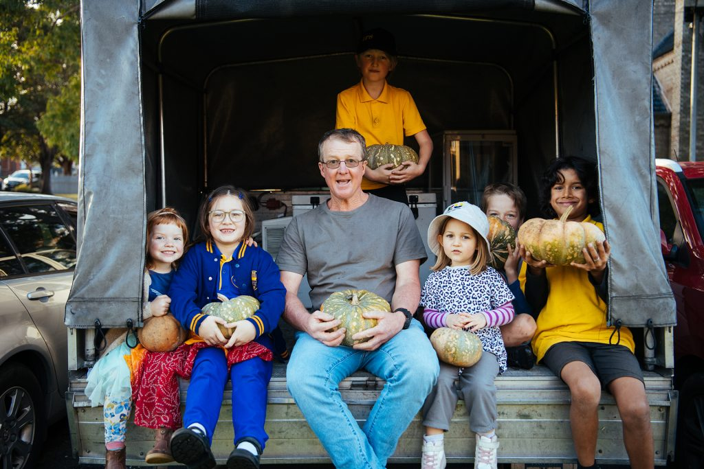 Man sitting in back of truck with children all holding pumpkins.
